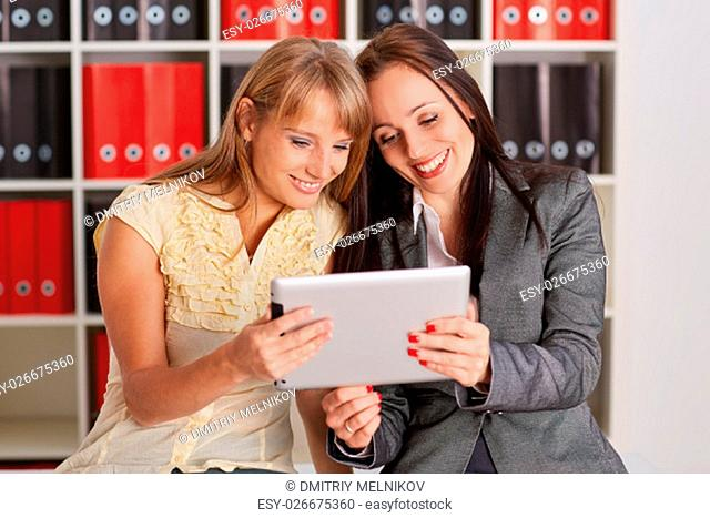Two young business women with computer tablet in the office