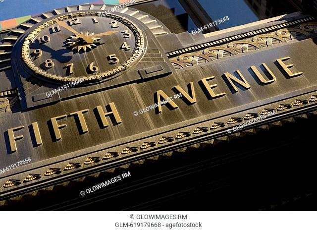 Low angle view of a clock and texts on a wall of a building, Fifth Avenue, Manhattan, New York City, New York State, USA