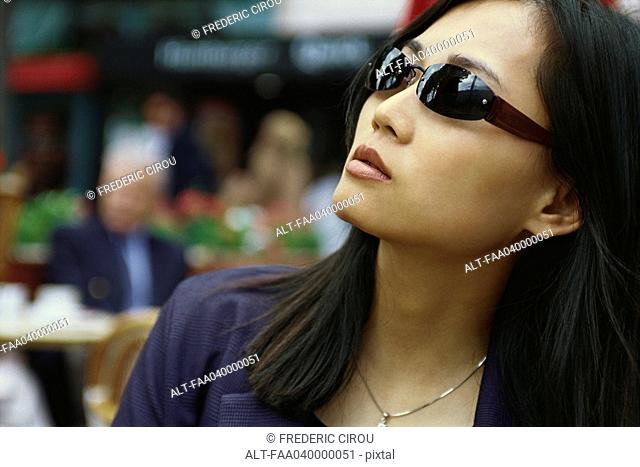 Woman wearing sunglasses, looking up