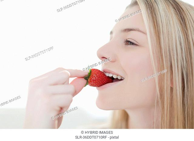 Smiling woman eating strawberry