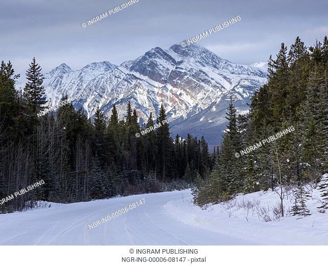 Snow covered road leading toward mountain range, Maligne Lake, Highway 16, Yellowhead Highway, Jasper, Jasper National Park, Alberta, Canada