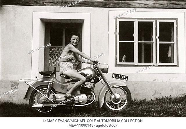 Lady wearing bikini on a 1958/9 250cc Puch motorcycle outside house circa 1959