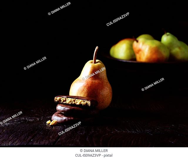 Comice pear cookies coated in dark chocolate, comice pears in bowl in dark background