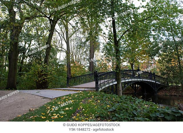 Amsterdam, Netherlands. Small stream and creek, running underneath a 19th century Vondelpark during summer season. Vondelpark has a great history and is one of...