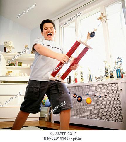 Happy Hispanic boy holding trophy in bedroom