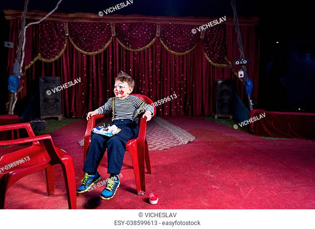 Full Length of Boy Wearing Clown Makeup Sitting in Red Plastic Chair with Tray of Make Up on Lap, on Empty Stage with Red Floor and Curtain in Background