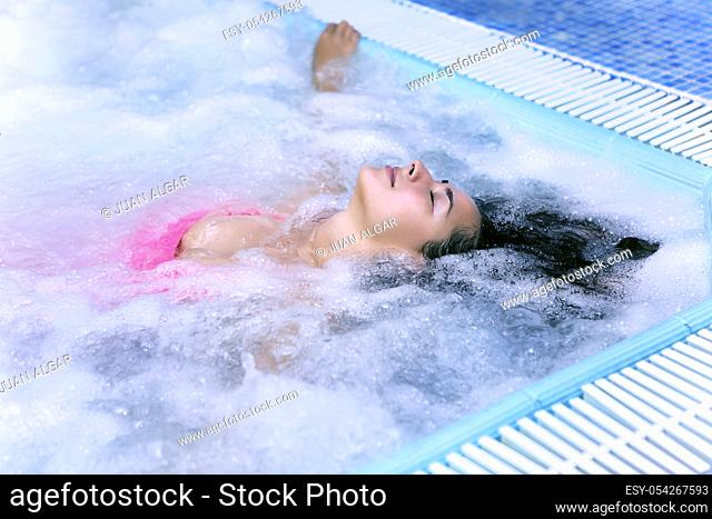 Young woman with eyes closed in pool with air bubbles. Horizontal indoors shot
