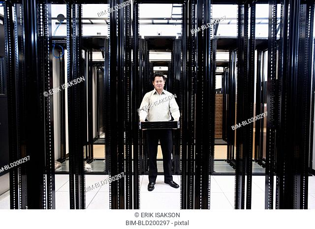 Asian businessman standing in empty server room