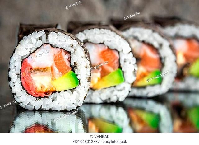 Sushi roll with salmon, shrimps and avocado over cocnrete background