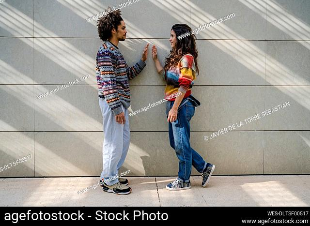 Couple of dancers face to face in front of a wall