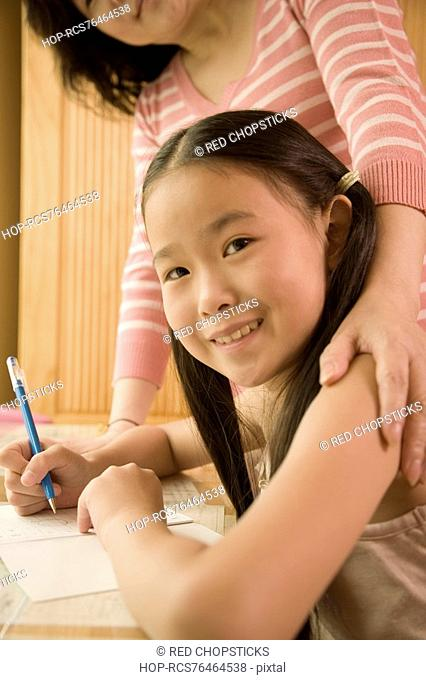 Side profile of a girl holding a pen with her mother standing beside her