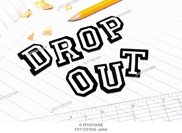 Varsity font stickers spelling out Dropout atop a lined paper notebook with ruler and pencil