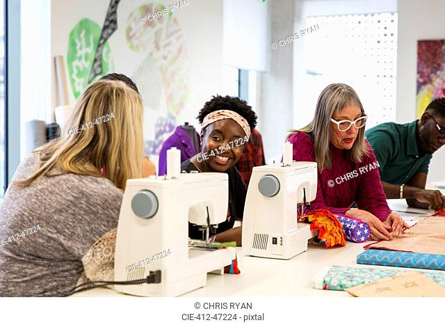 Female fashion designers working at sewing machines in studio
