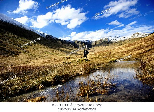 View of a person hiking in a mountain landscape at The Loch Lomond & The Trossachs National Park, Scotland, UK