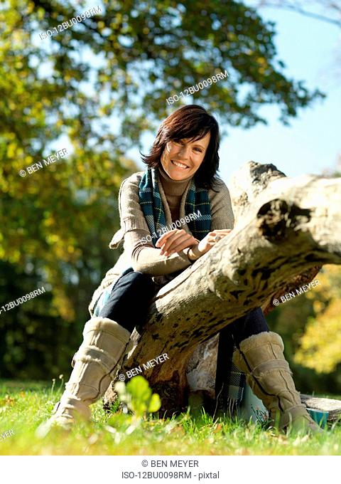 Woman sitting on log in Autumn