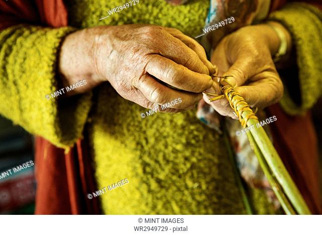 Close up of woman weaving a basket in weaver's workshop