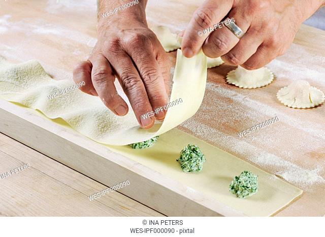 Producing homemade tortelloni with spinach ricotta filling, close-up