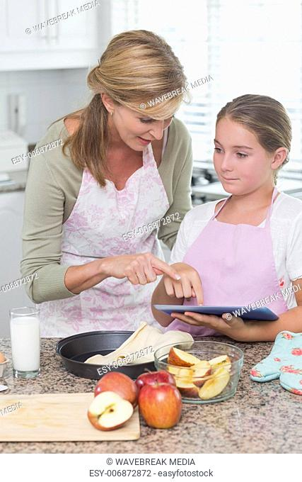 Happy mother and daughter preparing cake together