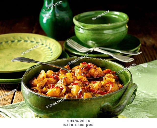 Mediterranean potatoes with peppers and spices in green vintage bowl