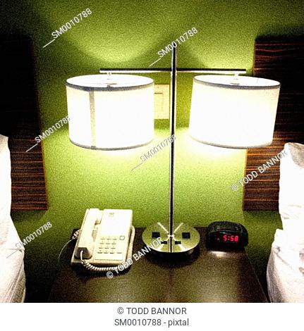 Hotel nightstand, telephone, clock and reading lamp