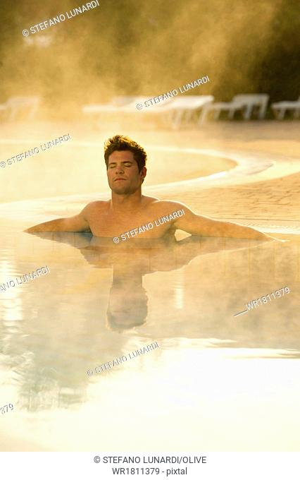 Young man in health club swimming pool
