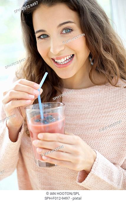MODEL RELEASED. Woman drinking a fruit smoothie with a drinking straw