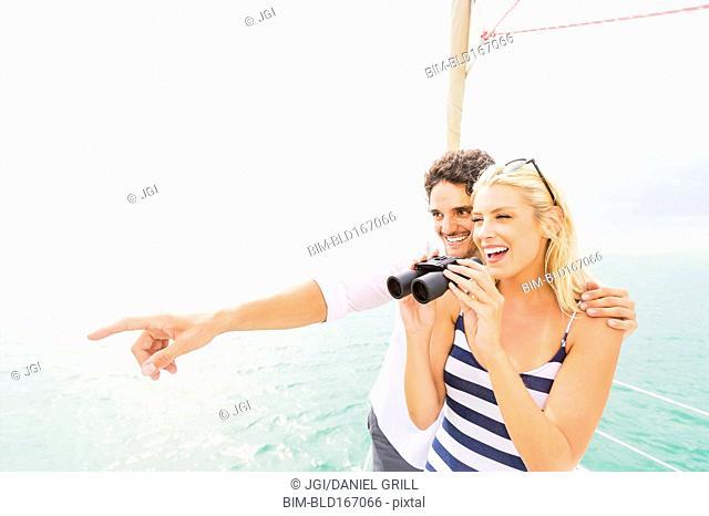 Couple looking out from boat deck with binoculars