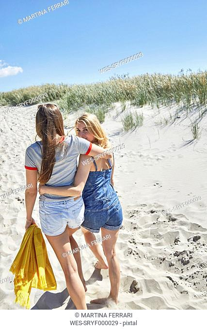 Two female friends walking arm in arm on the beach