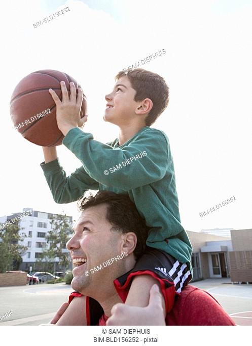Caucasian father carrying son with basketball on shoulders