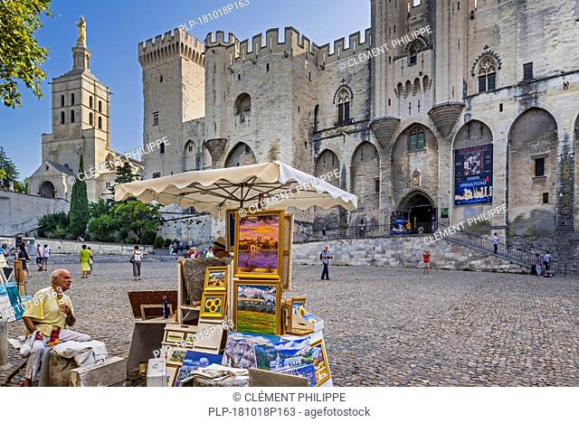 Artist selling paintings in front of the Palais des Papes / Palace of the Popes in the city Avignon, Vaucluse, Provence-Alpes-Côte d'Azur, France