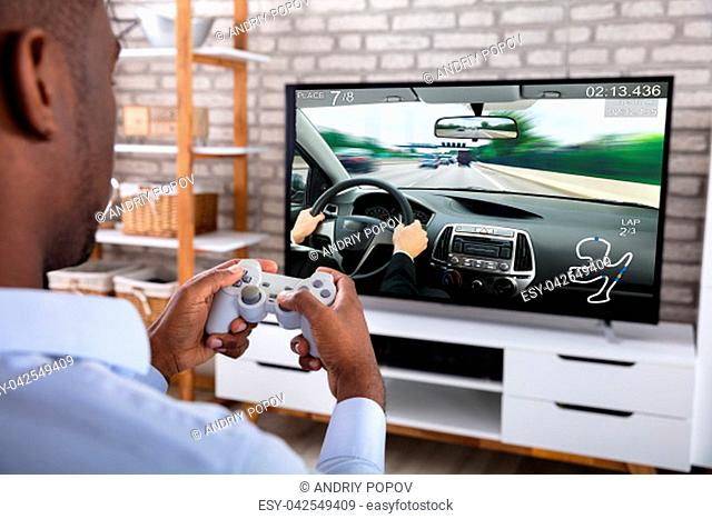 Close-up Of An African Man Playing Racing Game With Joystick On Television