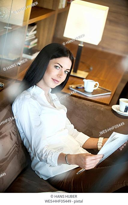 Reading woman sitting in hotel lounge, drinking coffee