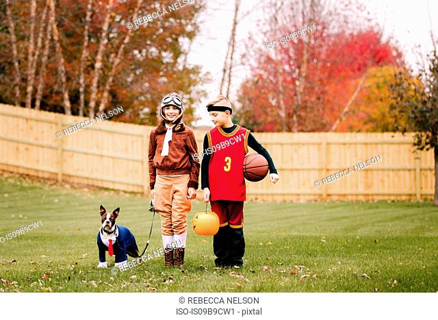 Portrait of boy, twin sister and boston terrier wearing halloween costumes in garden