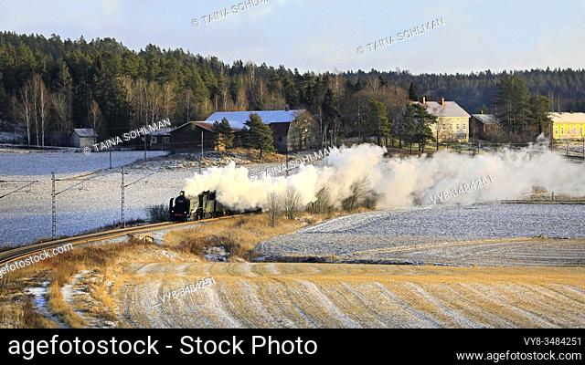 Steam locomotive Ukko-Pekka 1009 pulling carriages on a winter morning through rural scenery in Paimio, Finland. December 27, 2019