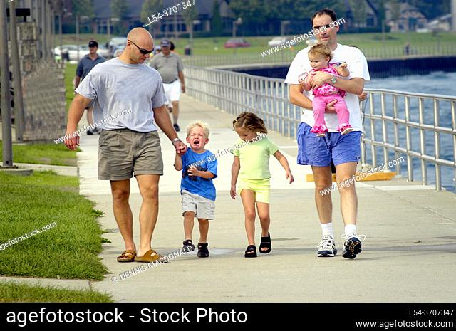 Two fathers walk with children on a boardwalk one child is crying