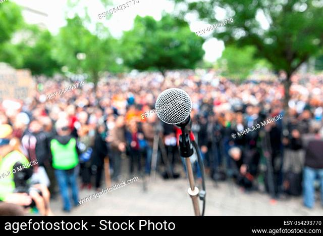 Protest. Public demonstration. Microphone in focus against blurred audience