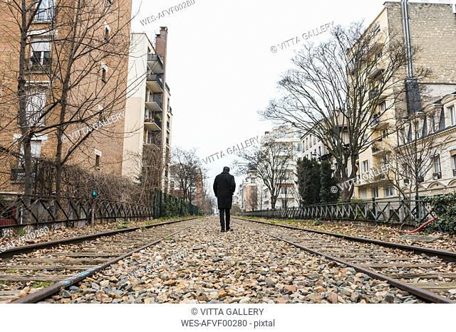 France, Paris, back view of man walking along abandoned railway tracks