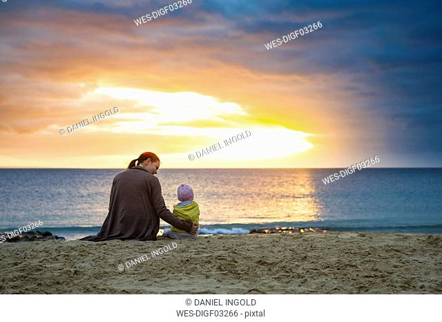 Mother with little daughter sitting on the beach at sunset