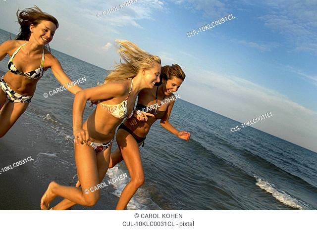 Girl teenagers running on the beach