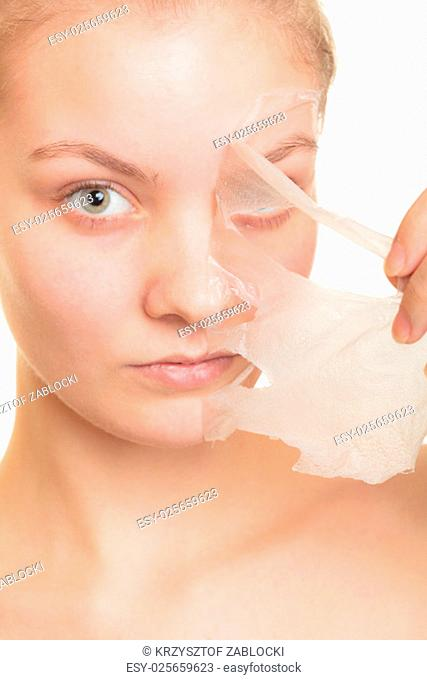 beauty skin care cosmetics and health concept. closeup of a young woman face,girl removing facial peel off mask isolated on white. peeling