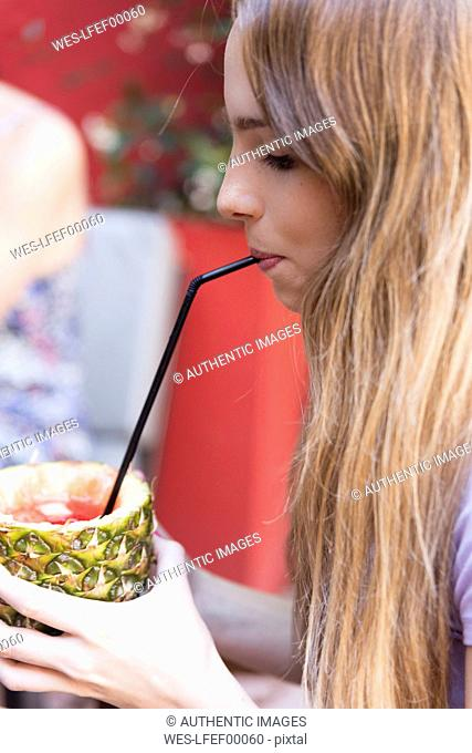 Young woman drinking a cocktail in pineapple outdoors