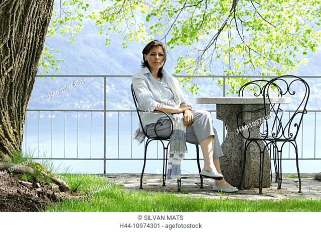 Woman sitting in a patio with sea view in Ticino, Switzerland