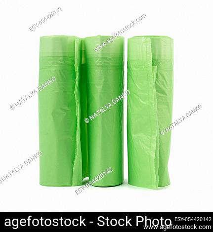 three rolls with green plastic bags for trash bin isolated on white background, close up