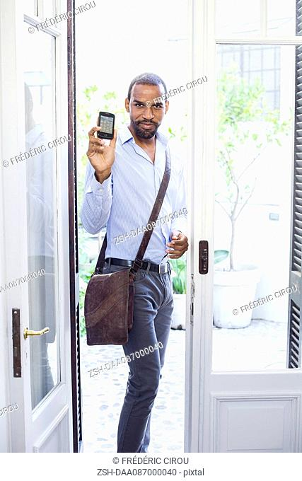 Man standing in open doorway, showing smartphone and smiling