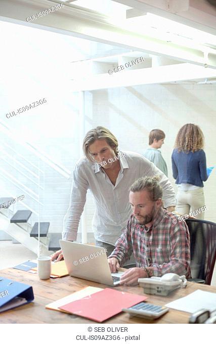 Two men looking at laptop in creative studio