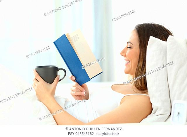 Side view portrait of a happy person reading a book lying on the bed at home
