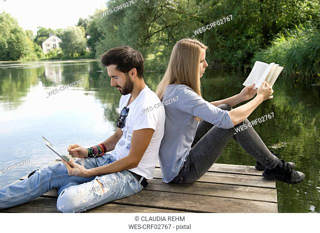 Young couple sitting on jetty at a lake with book and tablet
