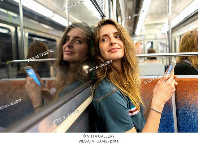 Portrait of smiling young woman and her mirror image in underground train