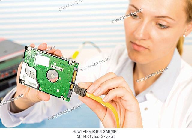 Female technician repairing circuit board