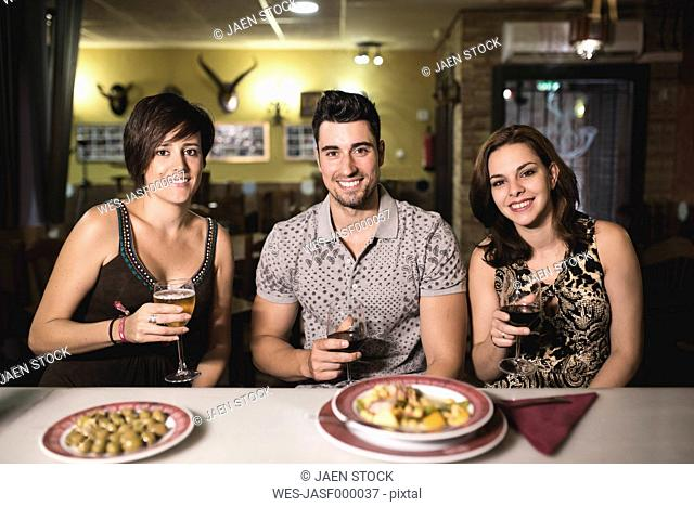 Portrait of three smiling friends in a restaurant